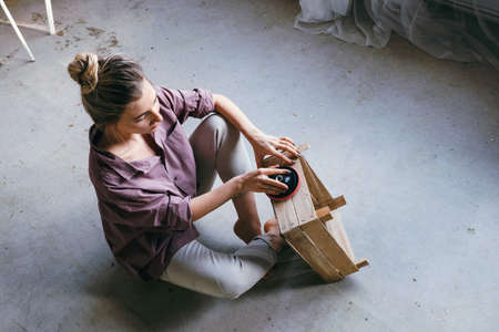 Portrait of a young woman sitting on the floor polishing a wooden box. DIY and hobby concept.
