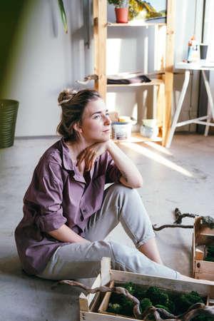 Beautiful woman artist sitting in art studio. Portrait of beautiful caucasian woman.