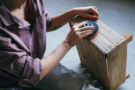 Close up hands of young woman sitting on the floor polishing wooden box. DIY and hobby concept. Banco de Imagens