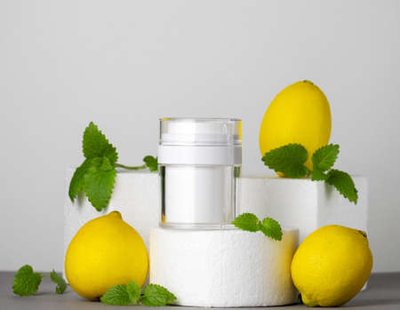 Facial cream white mock up jar on a product stand with lemon and mint leaves