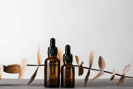 Brown glass bottles with essential oil on a gray background