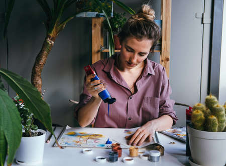 Young woman drawing in art studio with a lot of green plants. Arts and hobby concept.