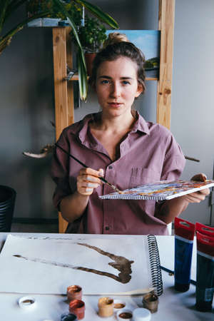Beautiful woman drawing in art studio. Hobby and art concept. Banco de Imagens