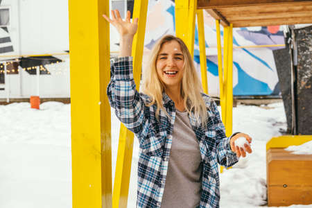 Beautiful young blonde hair woman playing with snow and watching in a camera outdoor Banco de Imagens