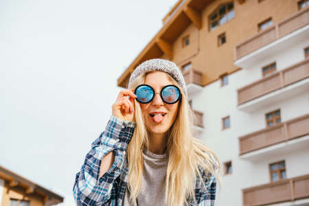 Young happy woman wearing sunglasses. Cool hipster woman portrait outdoor