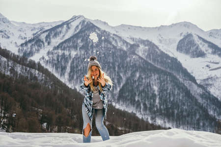Young beautiful woman playing with snow in the mountains. Selective focus.