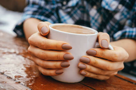 Close-up beautiful female hands hug white cup with hot drink on a wooden table outdoor. Stock Photo