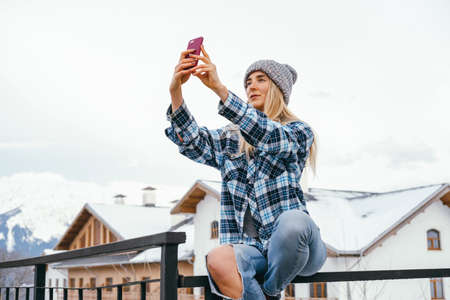 Beautiful young woman making selfie on a background of winter mountains and hotels. Winter travel concept. Banco de Imagens - 164980642