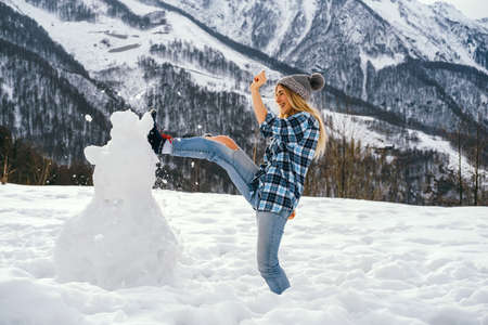 Young woman dressed in casual clothes kicks a snowman against the backdrop of mountains. Winter fun concept. Stock Photo