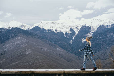 Beautiful young woman on a background of snowy mountains Banco de Imagens