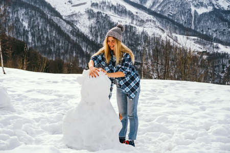 Positive young woman sculpts snowman on a background of snowy mountains