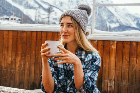 Beautiful sexy blond woman wearing knitting hat and holding hot drink mug outdoor on a wooden terrace in winter mountains