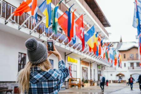 Young woman taking pictures in European travel. Solo travel and using technology concept.