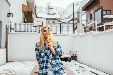 Happy young woman with ice cream on a background of snowy yard in mountain resort