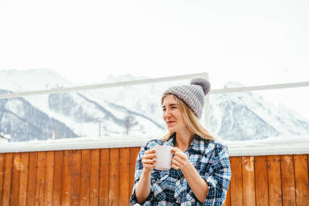 Positive portrait of young woman drinking hot drink on a blurred mountains background.