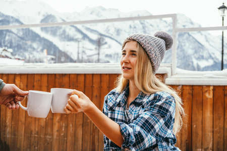 Young beautiful blonde girl in a knitted hat holds a cup of drink and clink with a man