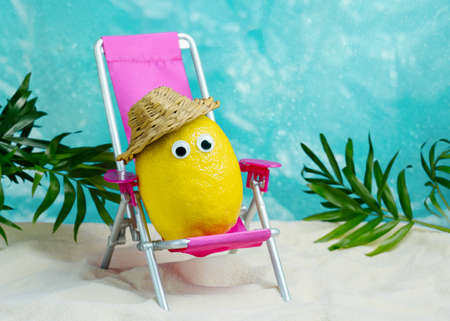 Lemon in hat relaxes on lounge chair on beach. Summer tropical minimal humor poster. Stock Photo