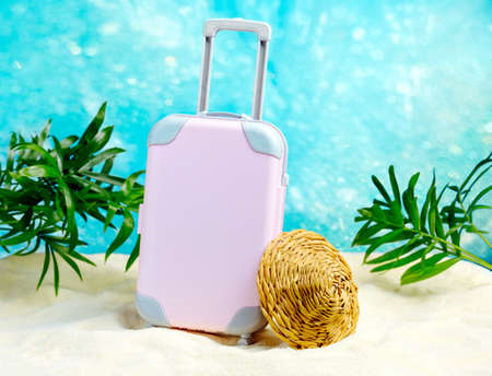 Pink plastic suitcase and straw hat on the white sand against the blue sea. Travel concept.
