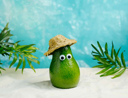 Cute avocado wearing straw hat relaxing on a tropical beach. Summer sale minimal poster.