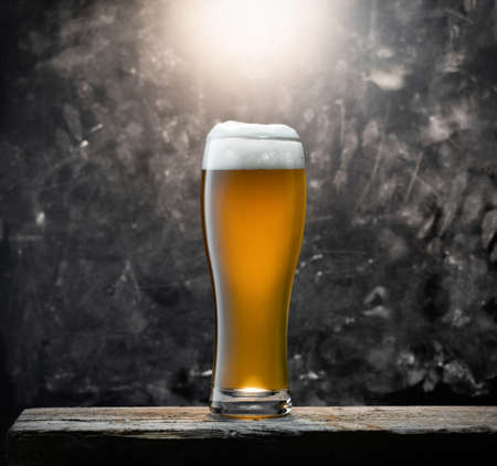 Glass of fresh beer on a wooden table on a background chalkboard in a bar Stock Photo