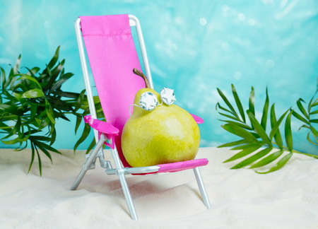 Cute pear in sunglasses relaxes on a beach chair. Summer tropical minimal humor poster.