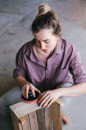 Portrait of a young woman sitting on the floor polishing a wooden box. DIY and hobby concept. Banco de Imagens - 166090282