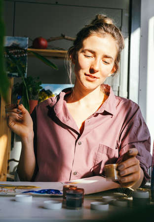 Beautiful woman drawing in art studio. Hobby and art concept. Standard-Bild