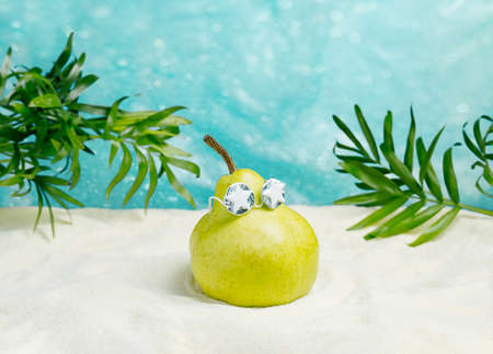 Cute pear in sunglasses on a tropical summer beach. Summer minimal poster design idea.