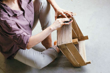 Close up hands of young woman sitting on the floor polishing wooden box. DIY and hobby concept. Stock Photo