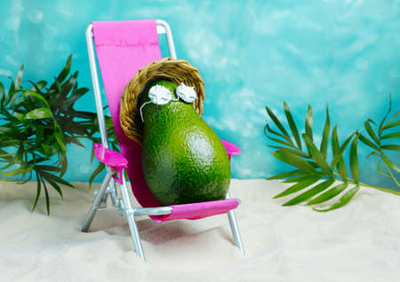 Avocado in hat and sunglasses relaxes on lounge chair on beach. Summer tropical minimal humor poster.