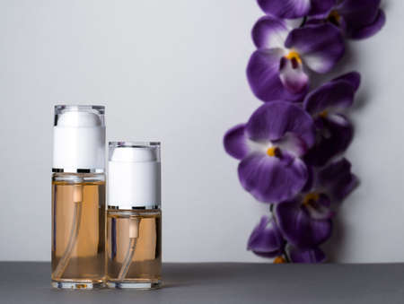 Perfume bottles and orchid gray background Stock Photo