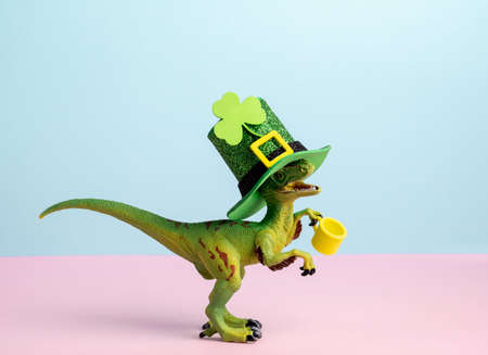 Cute st. Patrick card with dinosaur wearing green hat and holding green ale pastel pink and blue background Stock Photo