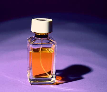 Perfume transparent bottle on a violet background
