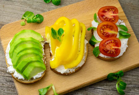 Top view toasts with avocado, bell pepper, tomatoes and cottage cheese wooden background. Healthy food concept. Stock Photo