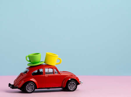 Cute red car with coffee cups on a roof, coffee and tea delivery