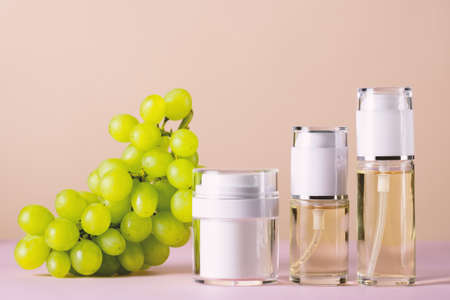 Cosmetic products set with green grape essential, mock up containers, copy space