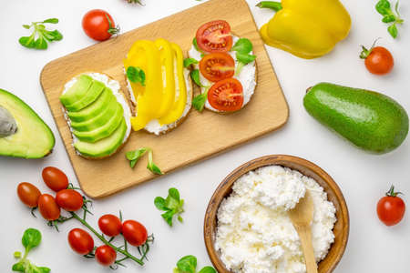 Top view toasts with avocado, bell pepper, tomatoes and cottage cheese white background. Healthy food concept.