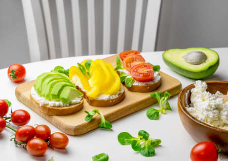 Toasts with avocado, bell pepper, tomatoes and cottage cheese white table. Healthy breakfast concept.