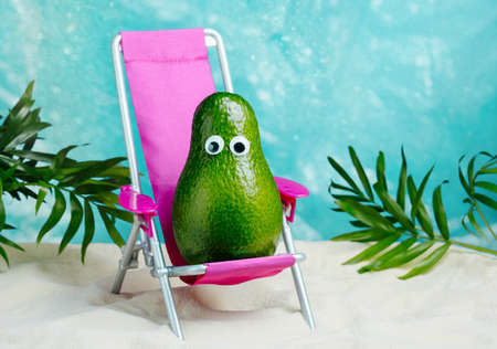 Avocado relaxes on lounge chair on beach. Summer tropical minimal humor poster. Standard-Bild
