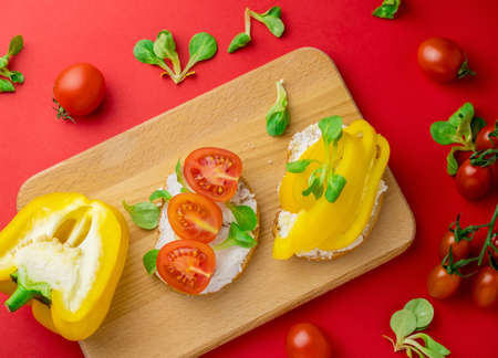 Top view toasts bell pepper, tomatoes and cottage cheese red background. Healthy food concept.