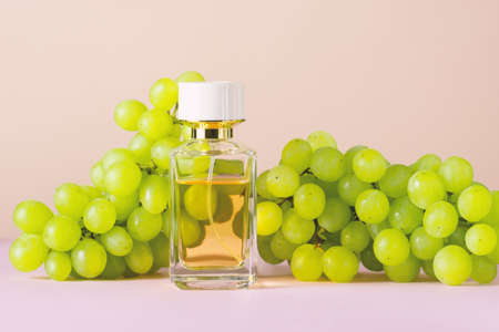 Perfume bottle with green grape berries pastel background