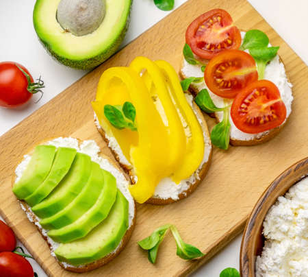 Close up toasts with avocado, bell pepper, tomatoes and cottage cheese white background. Healthy food concept. Stock Photo