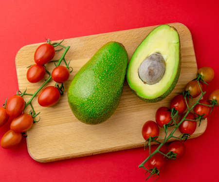 Top view flat lay avocado and cherry tomatoes red background. Organic healthy food.
