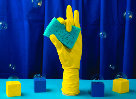 Cleaning gloves holding sponge on a blue background. Cleaning concept modern still life. Stock Photo