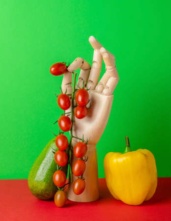 Modern still life with wooden hand and fresh vegetables on a green red background Stock Photo