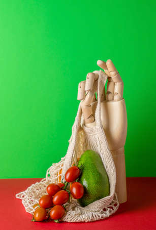 Modern still life with wooden hand, string bag and fresh vegetables on a green red background Stock Photo