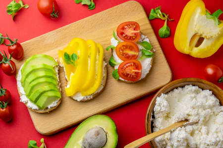 Top view toasts with avocado, bell pepper, tomatoes and cottage cheese red background. Healthy food concept.