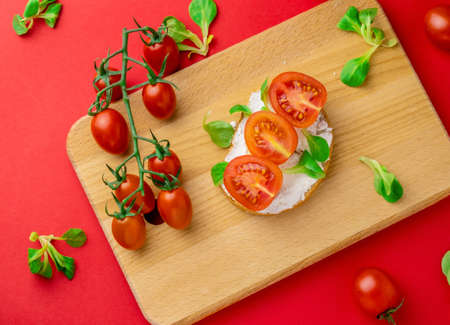 Top view flat lay toast with cottage cheese and sliced cherry tomatoes wooden board red background, healthy food concept