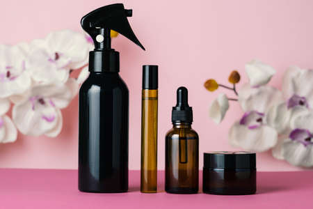 Brown glass bottles cosmetics set on a pink background. Beauty care concept.