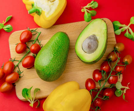 Top view flat lay avocado, pepper and cherry tomatoes red background. Organic healthy food. Banco de Imagens